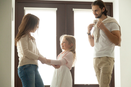 Foto de Caring mother helping little daughter dressing for walk with dad, family talking getting ready to go out standing in house hall, divorced young couple shared parenting and joint custody concept - Imagen libre de derechos