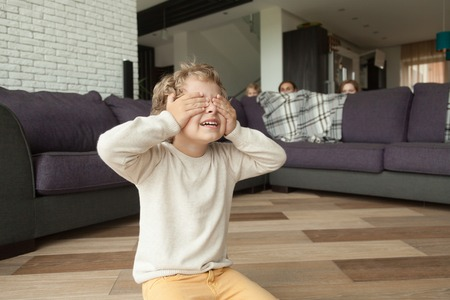 Photo for Kid boy playing hide and seek game at home, child closing eyes with hands counting while parents and sister hide behind sofa in living room peeking out, happy family having fun with children concept - Royalty Free Image