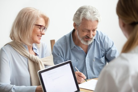 Photo for Happy senior couple about to sign document at meeting with financial advisor, older man agrees to put signature on contract making investment purchase, taking insurance, aged family in travel office - Royalty Free Image