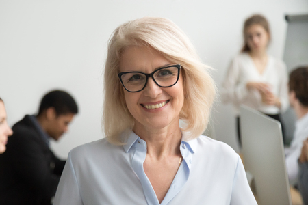 Photo pour Portrait of smiling senior businesswoman wearing glasses with businesspeople at background, happy older team leader, female aged teacher professor or executive woman boss looking at camera, head shot - image libre de droit