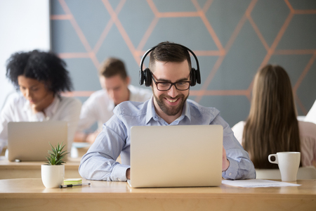 Photo for Smiling businessman wearing headphones watching video or consulting client online looking on laptop in office, happy millennial employee in headset making videocall using computer app in coworking - Royalty Free Image