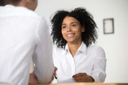 Photo pour Smiling african female hr employer interviewing male job applicant asking questions, black recruiter attentively listening to seeker, good first impression, human resources management concept - image libre de droit