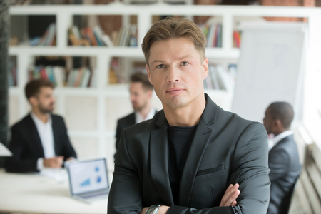 Photo pour Serious corporate worker looking at camera, company associates discussing business behind. Portrait of confident business man posing for company advertising in office. Concept of teamwork, leadership. - image libre de droit