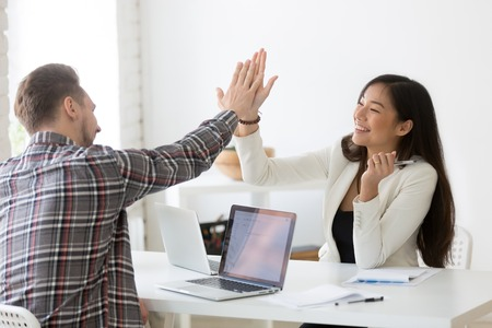 Photo pour Young asian and caucasian partners giving high five at workplace, diverse motivated colleagues celebrate goal achievement - image libre de droit