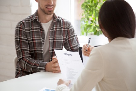 Photo for Hr manager reading smiling applicants resume at job interview, recruiter employer holding cv of confident vacancy candidate - Royalty Free Image