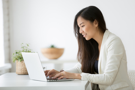 Foto de Smiling young asian businesswoman using computer at home office workplace - Imagen libre de derechos