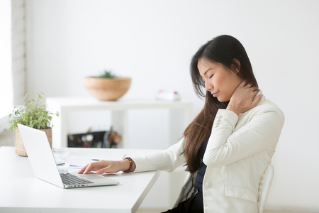 Photo for Young asian businesswoman touching massaging stiff neck to relieve pain in muscles after sedentary computer work in incorrect posture - Royalty Free Image