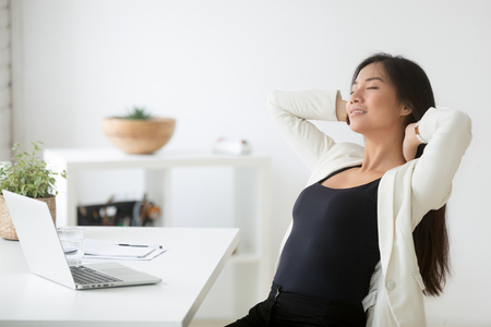 Photo pour Relaxed happy asian woman enjoying break at workplace - image libre de droit