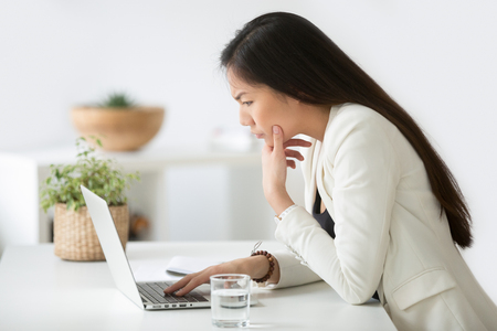 Photo pour Puzzled confused asian woman thinking hard concerned about online problem solution looking at laptop screen - image libre de droit