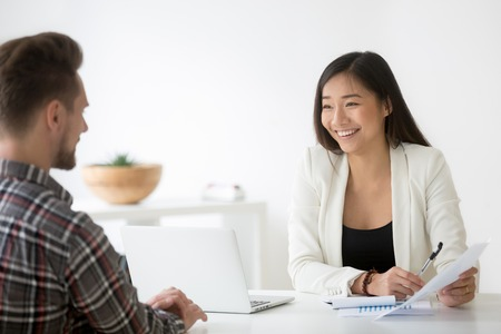 Photo for Friendly asian hr smiling laughing talking to candidate at job interview - Royalty Free Image