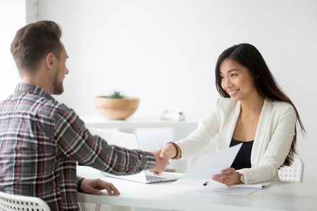 Photo for Happy asian businesswoman handshaking successful caucasian candidate holding employment agreement offering job contract - Royalty Free Image