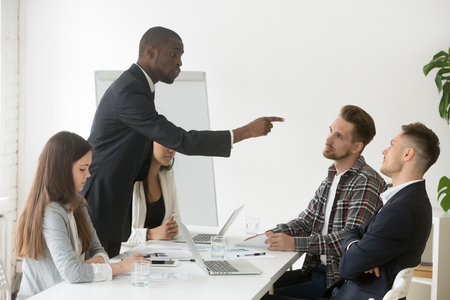 Photo pour Angry rude african businessman pointing finger threatens caucasian colleague at team meeting - image libre de droit