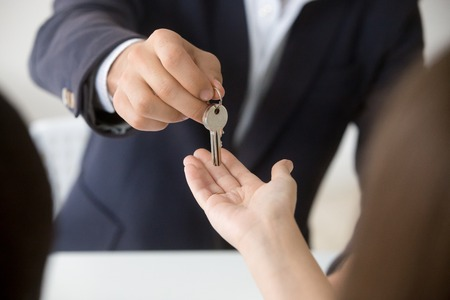 Photo for Realtor giving woman keys to new apartment, agent making deal with client buyer owner tenant renter buying or renting real estate - Royalty Free Image