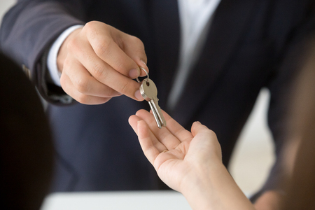 Foto de Female hand taking key from realtor buying renting new house, getting real estate ownership concept - Imagen libre de derechos
