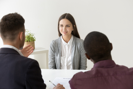 Photo for Confident female applicant smiling at job interview with diverse hr managers - Royalty Free Image