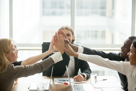 Foto de Excited happy multiracial business team giving high five at office meeting motivated by victory - Imagen libre de derechos