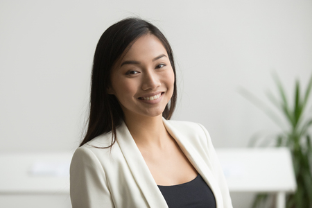 Photo pour Happy Asian office worker in formal wear smiling to camera posing for company business catalogue, making portrait photo. Confident businesswoman laughing with bright wide smile - image libre de droit