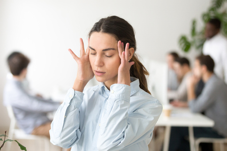 Foto de Stressed frustrated young woman employee feeling pain unwell dizzy, tired of difficult office job, suffering from panic attack, hormone imbalance or having headache migraine massaging temples at work - Imagen libre de derechos