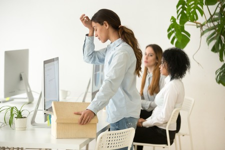 Photo for Upset dismissed young woman employee packing box at workplace on last working day, depressed stressed frustrated office worker preparing to leave after getting fired from job or laid off concept - Royalty Free Image
