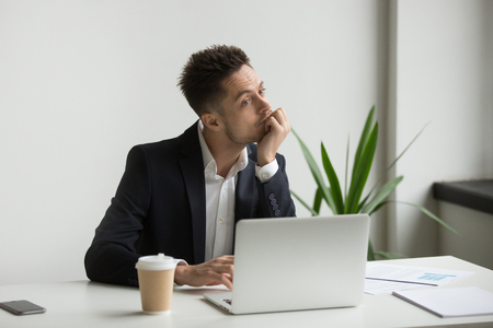 Foto de Bored tired millennial businessman in suit feeling dull working on laptop at workplace, absent-minded employee thinking or boring monotonous office routine, no motivation and lack of ideas concept - Imagen libre de derechos