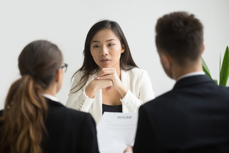 Photo for Confident asian female applicant convincing hr managers to hire her at job interview, young skilled chinese professional candidate talking to recruiters making first impression, employment concept - Royalty Free Image