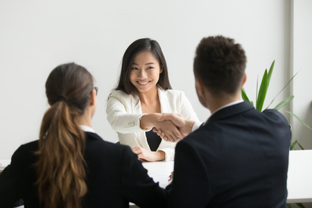 Foto per Happy millennial asian applicant getting hired shaking hand of hr, employer handshaking successful smiling chinese candidate congratulating with job interview win offering employment contract concept - Immagine Royalty Free