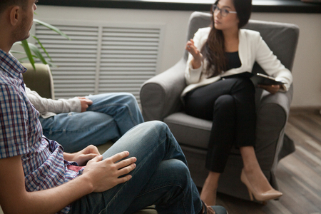 Foto de Asian psychologist counseling talking to unhappy couple in office, family counselor sexologist sitting in chair consulting family during therapy session, marriage and sexual problems solution concept - Imagen libre de derechos