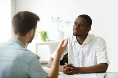 Foto de African American employer listening attentively to caucasian job applicant talking at work interview, being friendly and interested to candidate. Concept of recruiting, employment, hiring - Imagen libre de derechos