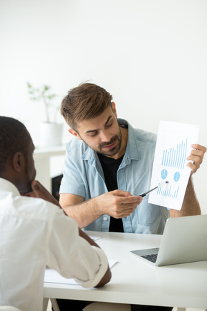 Photo for Thoughtful African American worker listening to Caucasian colleague presenting visual material, demonstrating growing rates, explaining strategy success. Concept of teamwork, cooperation - Royalty Free Image
