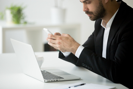 Foto de Businessman holding smartphone writing message working at laptop in office, typing business email on cellphone, texting to colleague, synchronizing cloud data. Concept of technology. Close up view - Imagen libre de derechos