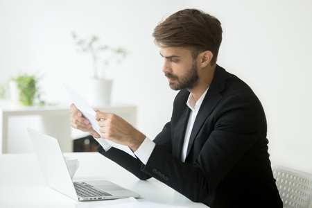 Photo pour Thoughtful businessman reading paper letter, considering contract conditions, analyzing business strategies. Serious entrepreneur looking through - image libre de droit