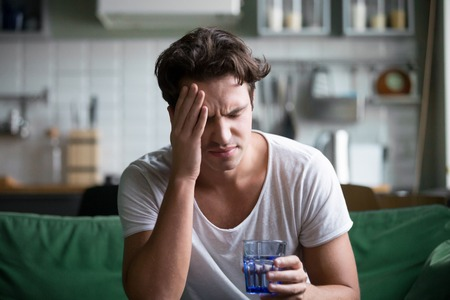 Foto de Young man suffering from strong headache or migraine sitting with glass of water in the kitchen, millennial guy feeling intoxication and pain touching aching head, morning after hangover concept - Imagen libre de derechos