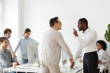 Photo pour Angry African American worker arguing with Caucasian middle aged mentor, having disagreement over work issues, multiethnic colleagues disputing and quarreling loudly at shared workplace - image libre de droit