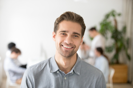 Photo pour Portrait of casual smiling Caucasian male worker laughing looking at camera, positive employee posing for company business catalogue with colleagues at background - image libre de droit