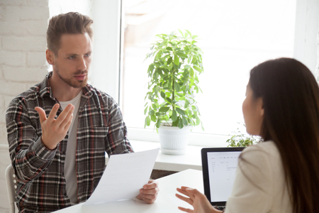 Foto de Serious dissatisfied male employee talking on bad contract terms and conditions, disagreeing with female employer on salary rate - Imagen libre de derechos