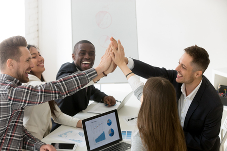 Photo for Excited diverse millennial group giving high five celebrating online business win or shared goal achievement, colleagues congratulating with good result, performing team building. Rewarding concept - Royalty Free Image