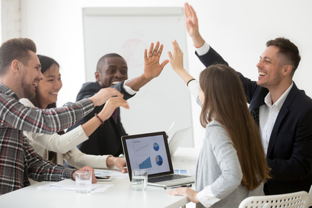 Foto de Excited diverse work team giving high five at board meeting, celebrating shared goal achievement, congratulating with win or good result, showing team spirit, unity. Concept of cooperation, rewarding - Imagen libre de derechos