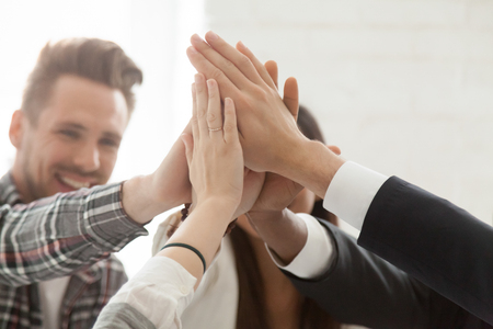 Foto de Close up of excited colleagues giving high five, celebrating shared goal achievement or win, performing team building, showing unity, workers greeting with successful project, good business results - Imagen libre de derechos