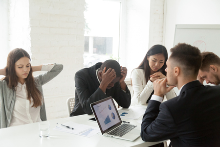Foto de Disappointed diverse millennial team feeling despair because of bad results or falling statistics, upset colleagues shocked by negative bankruptcy news at company meeting, trying to solve problems. - Imagen libre de derechos