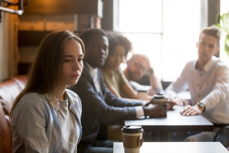 Photo pour Sad offended sitting alone in coffeeshop, ignoring people cheering her because of canceled date, female outcast not talking or listening to friends apologizing after bad joke. Bad relationship concept - image libre de droit