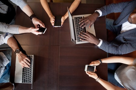 Foto de Top view of diverse gadget addicts using devices, not talking during friendly meeting, multiracial people lost in virtual reality, being obsessed with technology, busy with laptops and smartphones - Imagen libre de derechos