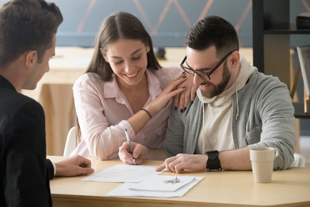 Foto de Excited millennial couple signing purchase agreement buying first home together, husband puts signature on document, becoming apartment owner, spouses legalize property ownership in realtor office - Imagen libre de derechos