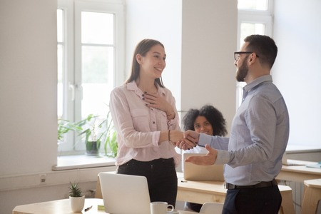 Photo for Male boss congratulating female employee handshaking and greeting her on special occasion, happy employer shaking hand of woman worker complimenting with promotion of good work results. Reward concept - Royalty Free Image