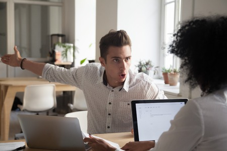 Foto de Mad male worker yelling at female colleague asking her to leave office, multiracial coworkers disputing during business negotiations, employees cannot reach agreement, blaming for mistake or crisis - Imagen libre de derechos