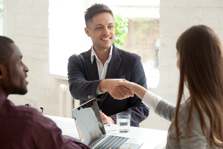 Photo for Smiling male worker shaking hand of young female colleague at business meeting, multiracial coworkers cooperating, partners handshaking greeting or making good first impression at briefing in office - Royalty Free Image