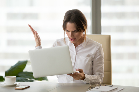 Foto de Angry businesswoman holding laptop, mad about gadget malfunction, furious employer feel nervous about error message or notification at computer screen, woman have software problem or failure - Imagen libre de derechos