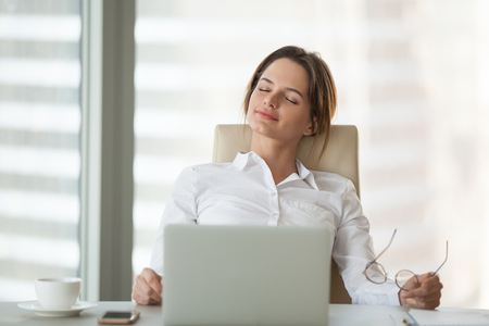 Foto de Relaxed businesswoman leaning in chair with eyes closed, resting and meditating in office, calm female ceo taking off glasses, relieving work stress, dreaming of future success and achievements. - Imagen libre de derechos