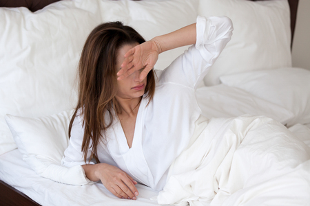 Foto de Frustrated young woman wake up in morning feeling bad, having bad sleep, sleepy millennial female have hangover and strong headache after sleepless night, girl suffer from bright light or sunny rays - Imagen libre de derechos