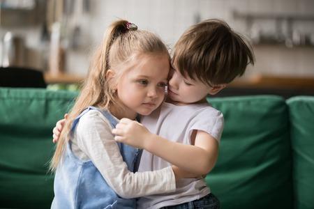 Foto de Little boy hugging consoling upset girl sitting on sofa, kid brother embracing sad sister apologizing or comforting, siblings friendship, preschool children good relationships and support concept - Imagen libre de derechos