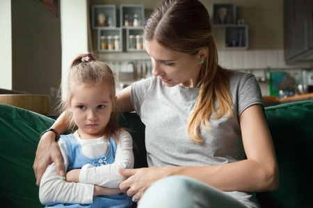Foto de Loving mother consoling or trying make peace with insulted upset stubborn kid daughter avoiding talk, sad sulky resentful girl pouting ignoring caring mom embracing showing support to offended child - Imagen libre de derechos
